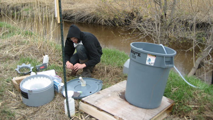 Ross prepares water samples after a rain fall. These carefully labeled samples will help tell the story of how the water moves during and after a rainstorm or snow melt. (Photo credit Janelle Laing.)